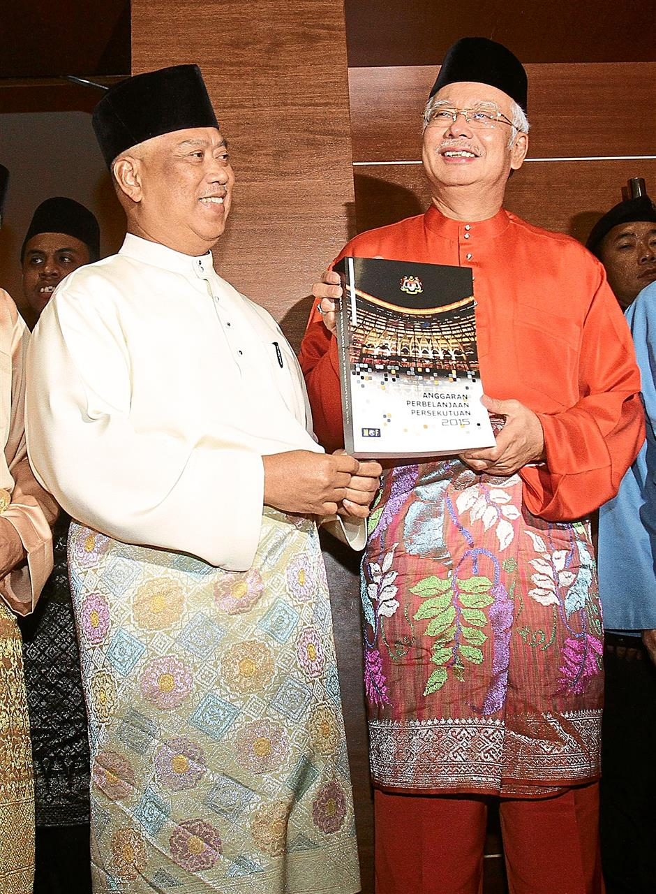 Moving forward: Najib (right) and Muhyiddin holding a copy of Budget 2015 after it was tabled in Parliament earlier this month.