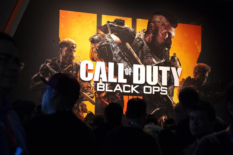 Attendees stand next to signage for Activision Blizzard Inc. Call Of Duty: Black Ops 4 video game during the E3 Electronic Entertainment Expo in Los Angeles, California, U.S., on Tuesday, June 12, 2018. For three days, leading-edge companies, groundbreaking new technologies and never-before-seen products is showcased at E3. Photographer: Troy Harvey/Bloomberg