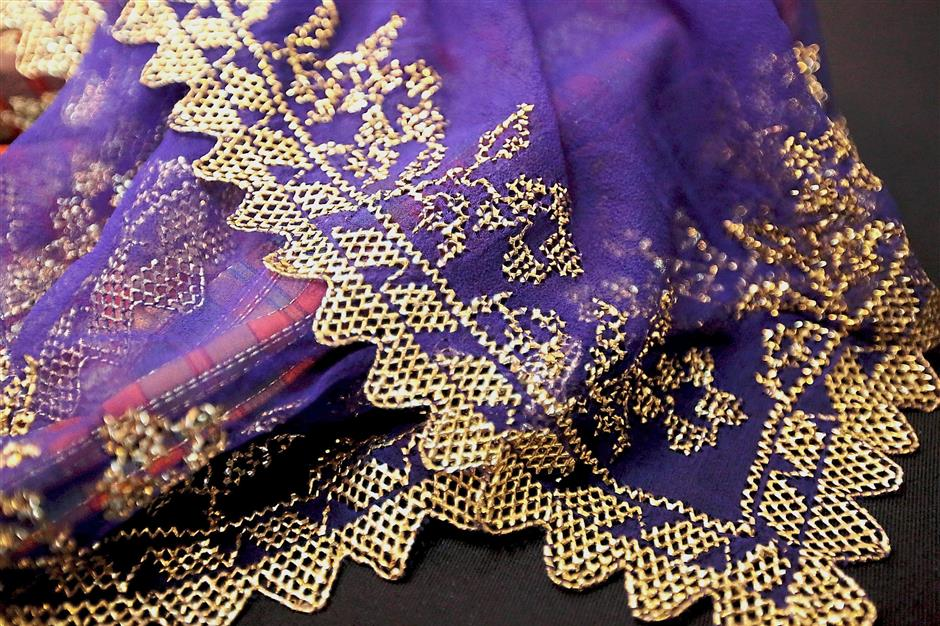 Another intricate piece of keringkam scarf golden embroidery handstitched on a purple background.