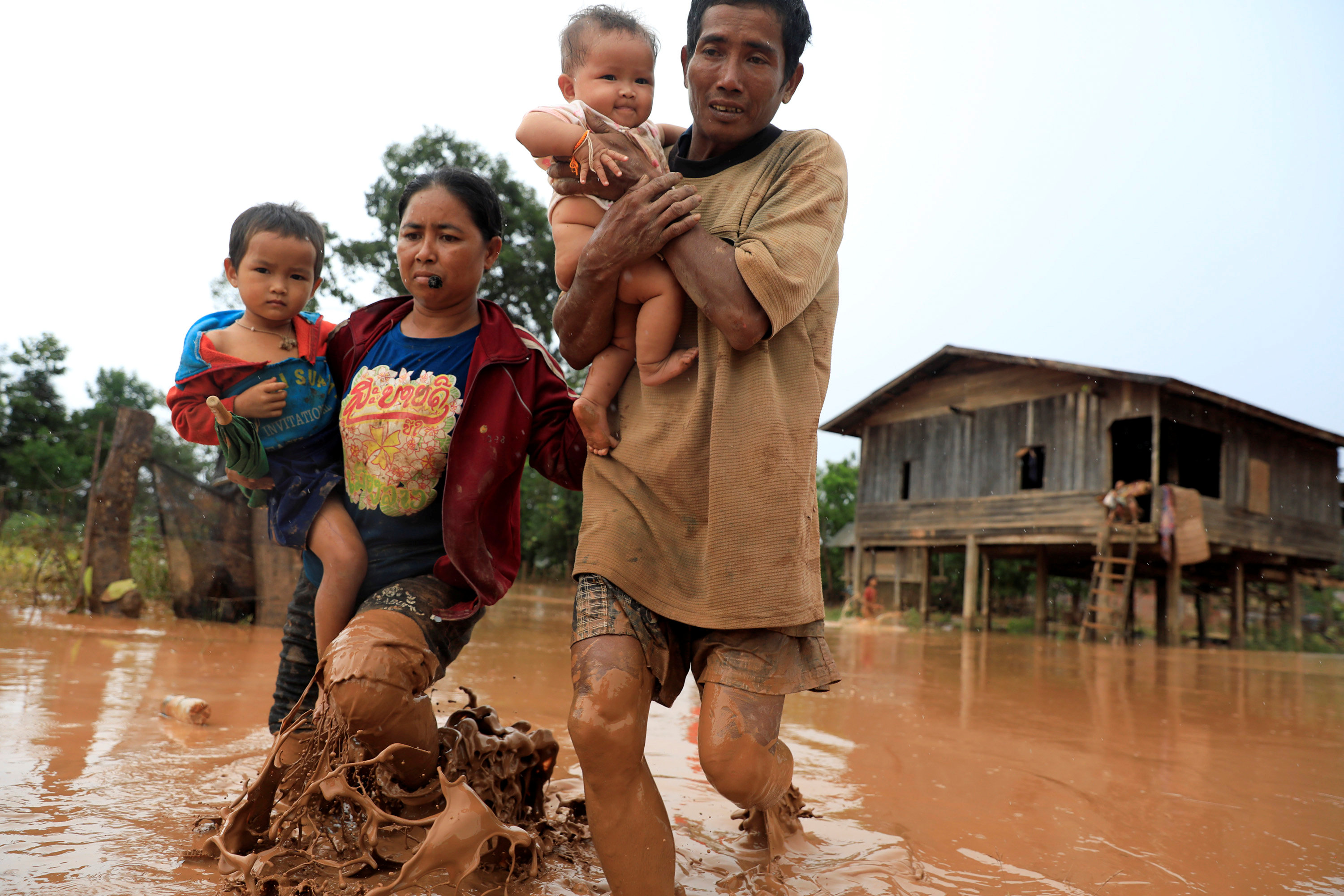 Parents carry their children as they leave their home during the flood after the Xepian-Xe Nam Noy hydropower dam collapsed in Attapeu province, Laos July 26, 2018. REUTERS/Soe Zeya Tun