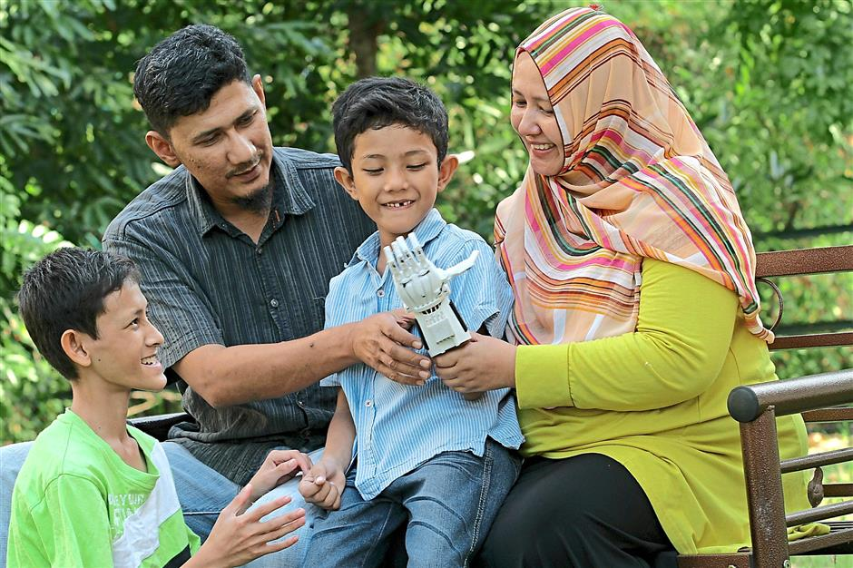 PIC FOR SHEELA CHANDRAN : Eight year old Muhammad Muqri Mifzal (centre) is all smiles being able to wear the new mechanical limb which was donated to him by Sujana Mohd Rejab. On left is brother Muhammad Adli Azmi, 16, father Rhemi Rizal and mother Nor Julaina Md Sani. 130215STAR PIC BY: / ZAINUDIN AHAD / The Star / 13 Feb 2015