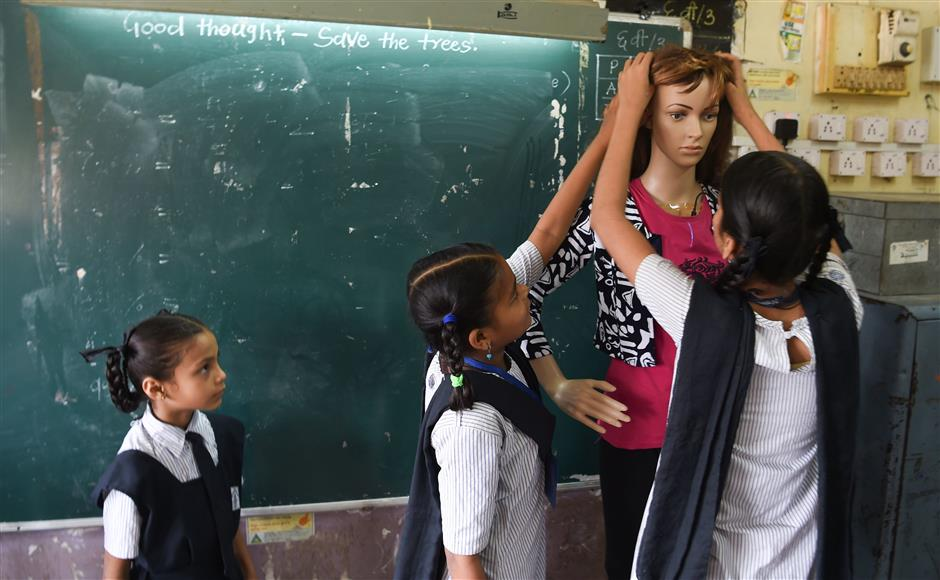 In this photo taken on February 6, 2019, an Indian student watches classmates put a wig onto a teaching virtual assistant mannequin fitted with Amazon's 'Alexa' -- a cloud-based intelligent voice service -- at the Ramakrishna Paramhansa Marg BMC school in Mumbai. - From a multi-billion-dollar education startup to wired-up mannequins, technology is helping to revolutionise the way Indian schoolchildren are learning -- provided their parents can afford it. (Photo by Indranil MUKHERJEE / AFP) / To go with 'INDIA-ECONOMY-EDUCATION-TECHNOLOGY-AMAZON',FOCUS by Vishal MANVE