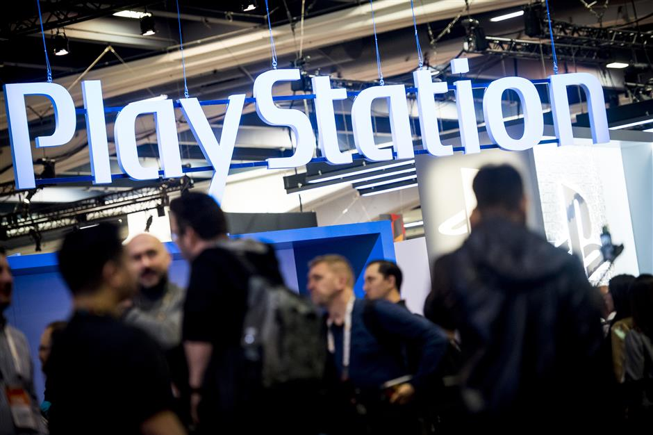 Attendees walk past the Sony Corp. Playstation display during the Game Developers Conference (GDC) in San Francisco, California, U.S., on Wednesday, March 21, 2018. The GDC is the world\'s largest professional game industry event that brings together game designers, programmers, artists, producers, and business professionals in the global game development community. Photographer: David Paul Morris/Bloomberg
