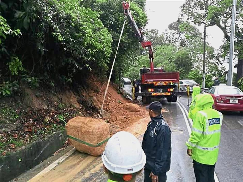 Authorities clearing a boulder that fell onto the road in Teluk Bahang — social mediapic. (Left) Flood victims wading through the waters in Hong Seng Estate in Penang.