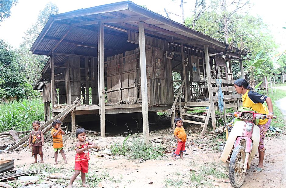 Open to the elements: Children playing near their flood-damaged house in Kampung Sentep, Kuala Betis. Kelantan. (Bottom) Alang drying bamboo sheets for the walls of his new house in the village.