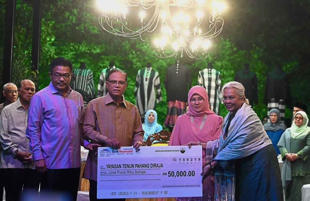 Tunku Azizah (second from right) looking on as Wan Rosdy presents a mock cheque to Fatimah.