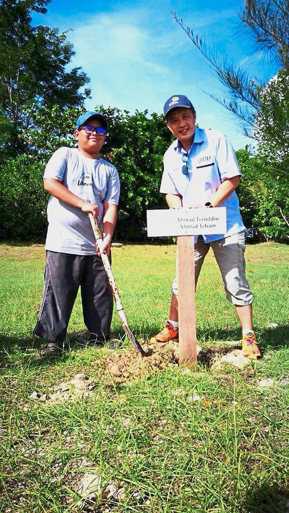 Iszuddin (left) and Yee putting up a signboard marking the 100m area adopted by the former.