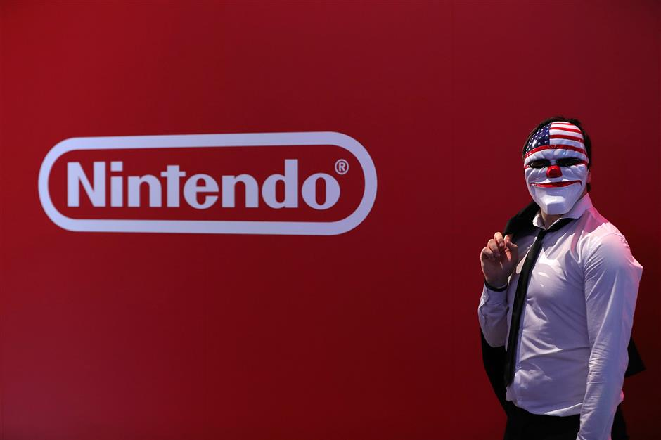 A gamer wearing a \'Stars and Stripes\' halloween mask poses beside a Nintendo Co. logo at the Gamescom gaming industry event in Cologne, Germany, on Tuesday, Aug. 21, 2018. Gamescom is Germany\'s largest congress revolving around digital games, and acts as an interface with other cultural and creative branches, as well as with the digital economy according to their media site. Photographer: Krisztian Bocsi/Bloomberg