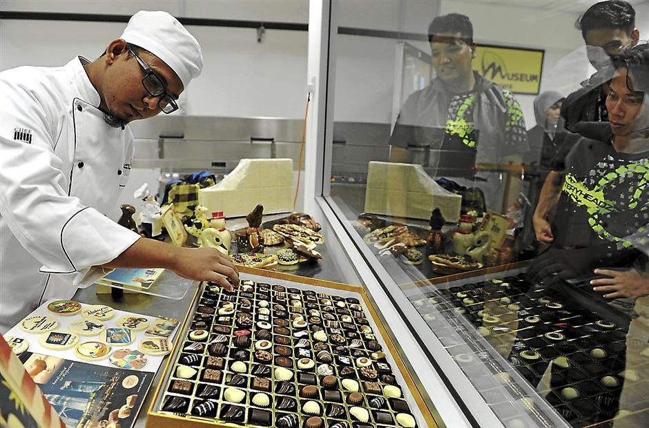 PETALING JAYA, 16 Jan -- Kakitangan Muzium Coklat, Mohd Yazid Hassan (kiri) menyusun pelbagai bentuk coklat sambil diperhatikan oleh pengunjung yang datang pada majlis pelancaran Muzium Coklat di Kota Damansara di sini hari ini.Menteri Pelancongan dan Kebudayaan Datuk Seri Mohamed Nazri Abd Aziz menyempurnakan majlis perasmian muzium tersebut hari ini.-- fotoBERNAMA (2014) HAKCIPTA TERPELIHARA