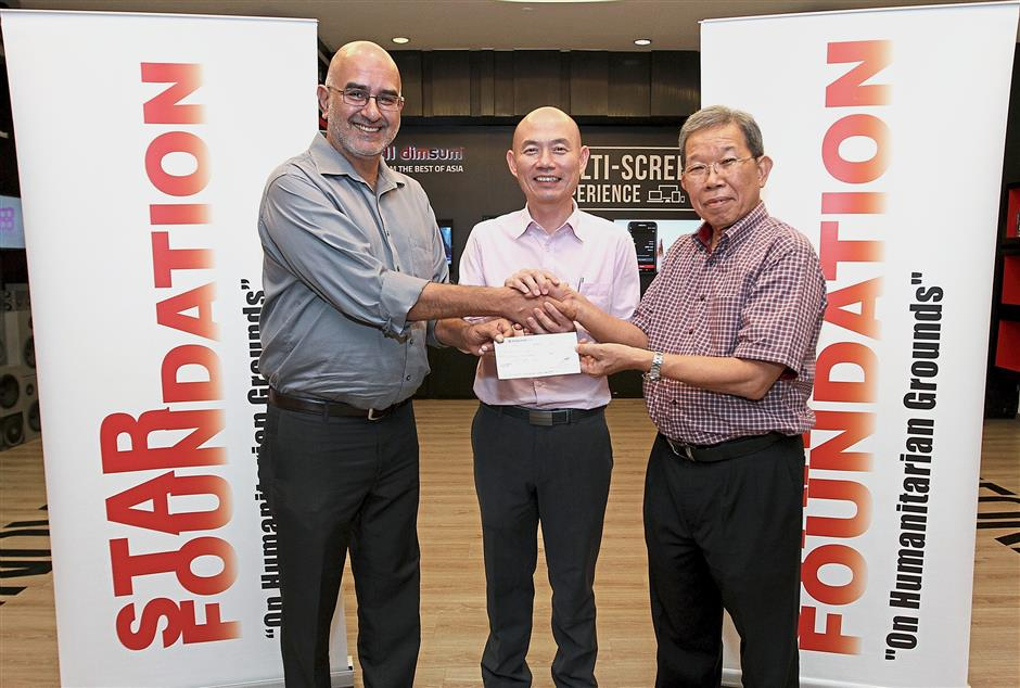 Lending a hand: Lim (centre) with Jagdev and Chuah, who was representing an anonymous donor who donated RM20,000 to the family of Yu Jian (inset).