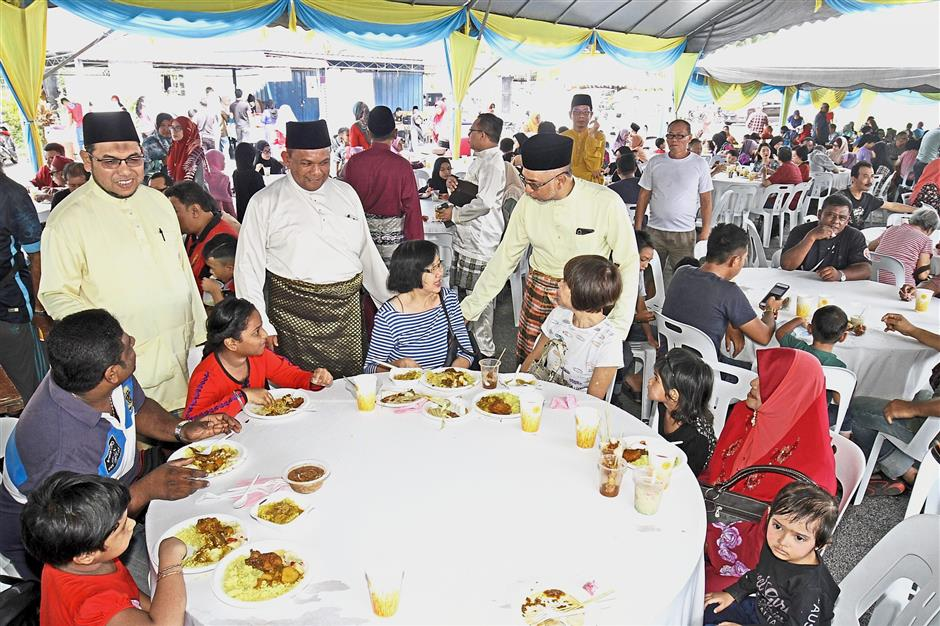 (From left, standing) Mohd Tuah, Zolkifly and Muhammad Bakhtiar chatting with guests during their joint Raya open house at Dataran Masjid An Nur, Titi Teras, Balik Pulau in Penang. — Photos: CHAN BOON KAI/The Star