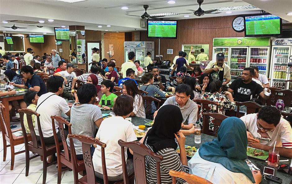 The crowd at Nasi Kandar Kayu in SS2, Petaling Jaya enjoying their meal while watching the match.