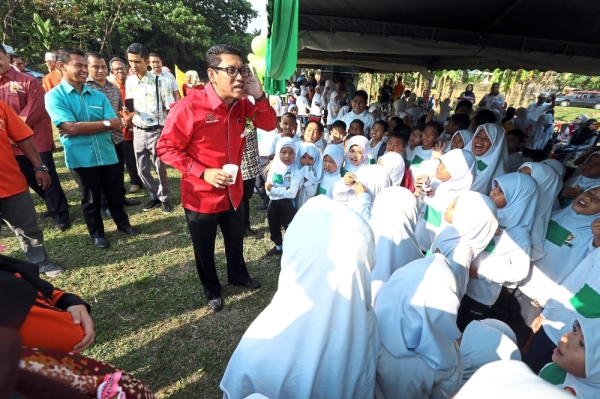 Ahmad Faizal (in red) mingling with students of Sekolah Agama Rakyat Al-Junid in Chemor during their sports day. u2014 RONNIE CHIN/The Star