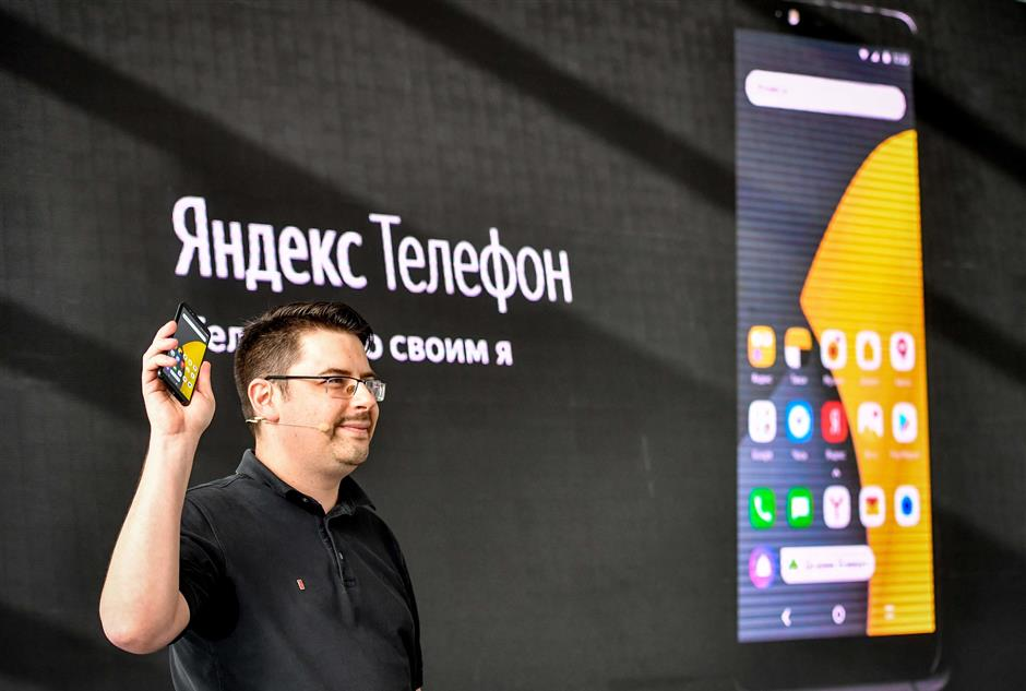 Yandex official Fyodor Yezhov presents a Yandex.Phone during a media event in Moscow on December 5, 2018. - Russian internet giant Yandex on December 5, 2018 launched its first ever smartphone, ending several weeks of suspense for tech fans over the highly anticipated launch. The new mobile device will go on sale on December 6, 2018 in Russia and online at a cost of 17,990 rubles ($269) and will work with the Android system. (Photo by Yuri KADOBNOV / AFP)