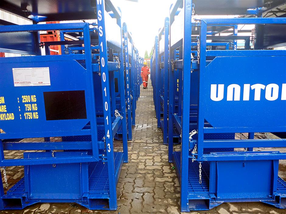 Final touch: A worker inspecting the containers before shipping out to their clients.