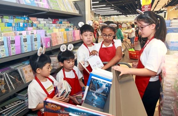 (From left) Little Store Assistants Chan Yan Jie, eight, Hayden Yap, seven, Lucas, Nachammai and Sam Shin Yee, 11, arranging books.