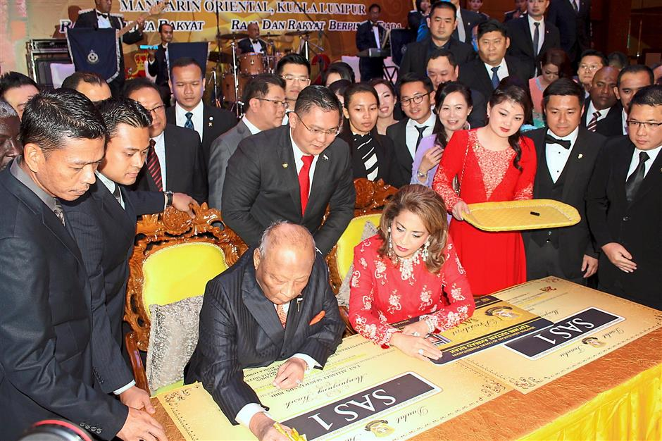 Sultan Ahmad Shah accompanied by Sultanah Kalsom signing a card to mark the launch of the SAS Privilege Club during the dinner.