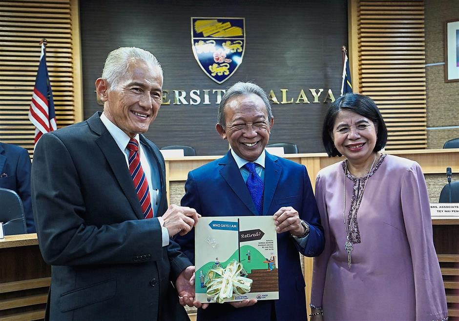 Samsudin (centre) holds the book, u201cWho Says I Am Retired?u201d together with Abdul Rahim (left) and Prof Norma.
