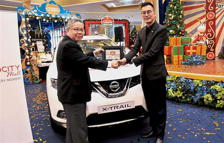 Wong (left) receiving the Nissan X-Trail 2.5l CVT from Edaran Tan Chong Motor marketing deputy general manager Phang Rick Kee.