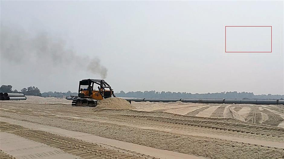 A tractor pushing sand on Pulau Indah where reclamation works are taking place.