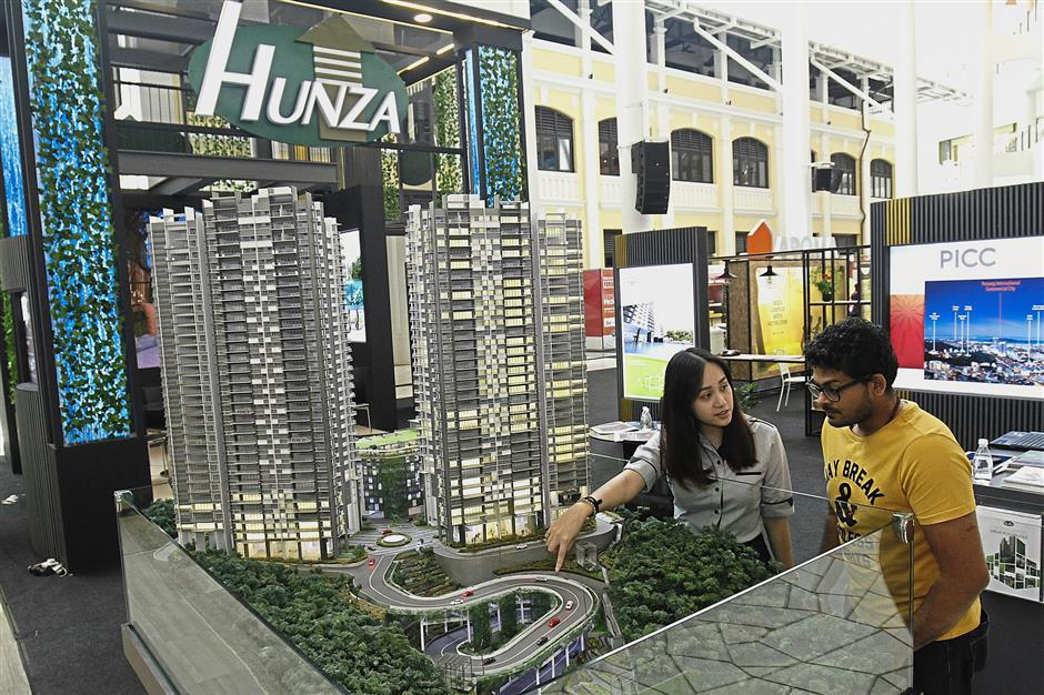 Hunza Properties Berhad sales & marketing executive Blair Teh Chee Yin (left) introducing the Alila2 project to Bushan.