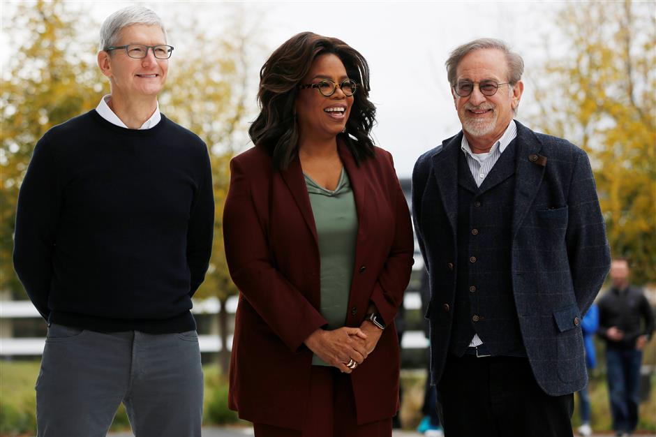 Apple CEO Tim Cook, Oprah Winfrey and director Steven Spielberg stand for a photo after the Apple special event at the Steve Jobs Theater in Cupertino, California, U.S., March 25, 2019. REUTERS/Stephen Lam