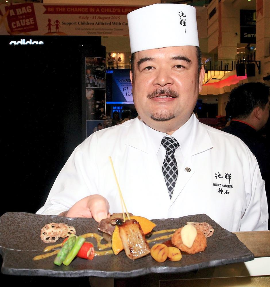 Iketery's Chef Ricky Kamiishi with his Miso Flavour Plate featuring Grilled Wagyu Beef, Foie Gras and Halibut preserved with Miso, Mushroom Risot Croquet and Miso Cream Sauce served with Paprika and Asparagus with Miso Mustard Sauce.