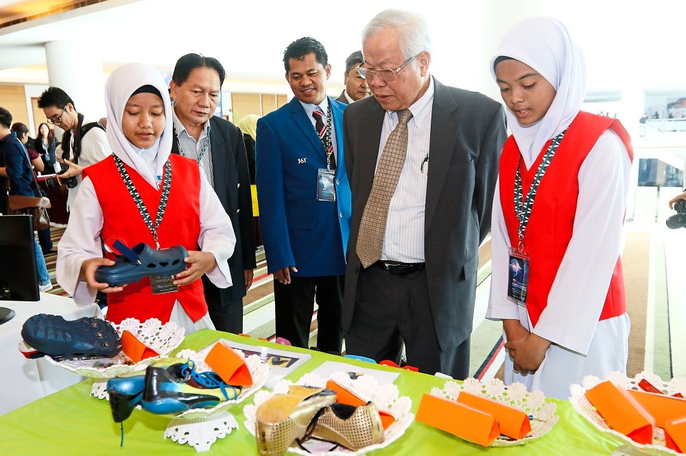 Manyin (second from right) looking at a display of students' work at the international conference on education transformation in Kuching. — Photos: ZULAZHAR SHEBLEE/The Star
