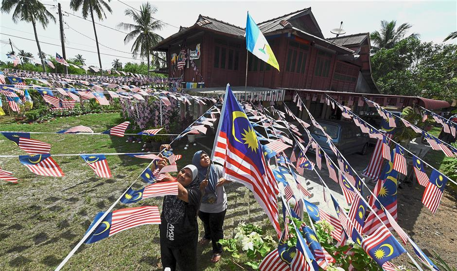 Standing out: Normala Md Desa (left) and her daughter Nurul Nadiah Tajuddin decorating the compound of their home in Kampung Perlis in Balik Pulau, Penang, with over 2,500 Jalur Gemilang flags for National Day. Normala says she has done this every August for the last 20 years. Helped by her husband and five children, the decorations cost about RM1,300. — Bernama