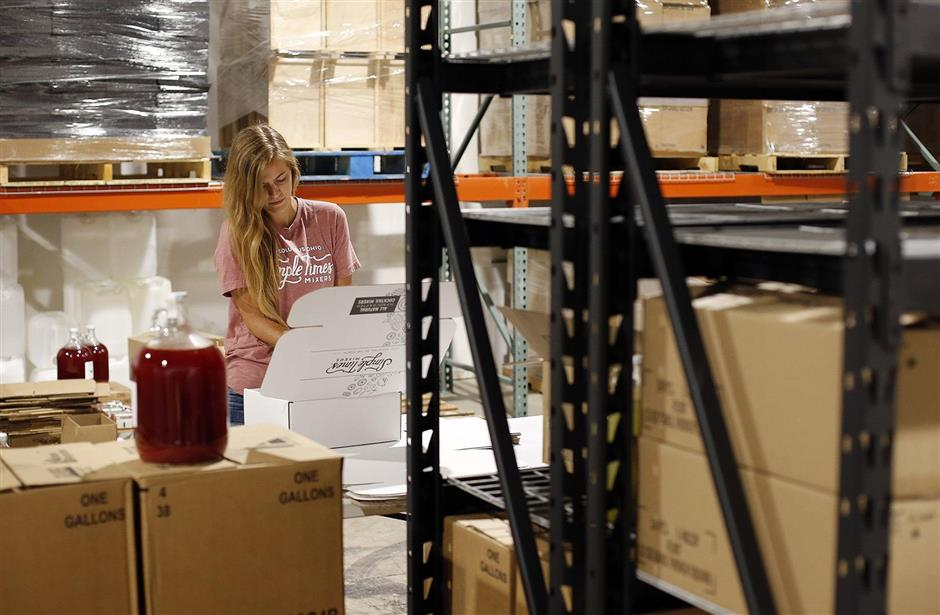 Maria Fehl packs a monthly subscription box with bottles of strawberry lemonade and blackberry mint lemonade at the Simple Times Mixers headquarters and production facility in Gahanna on Friday, July 19, 2019. (Adam Cairns/Dispatch/TNS)