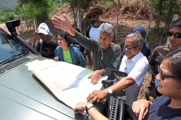 Meor Razak (in green) referring to a map showing the area where land clearing at Gunung Hijau Pusing, Perak, is taking place.