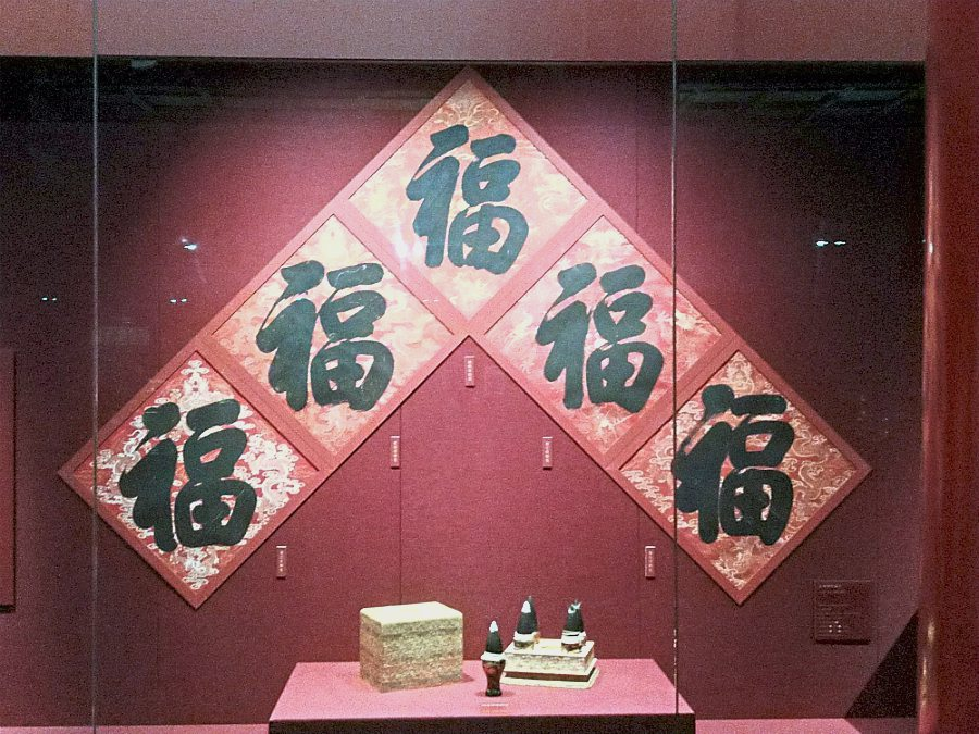 Down memory lane: (Top) The 'fu' character written by five Qing emperors, namely (from left) Daoguang, Qianlong, Kangxi, Yongzheng and Jiaqing. (Left) Visitors walking down a path decorated with red lanterns.