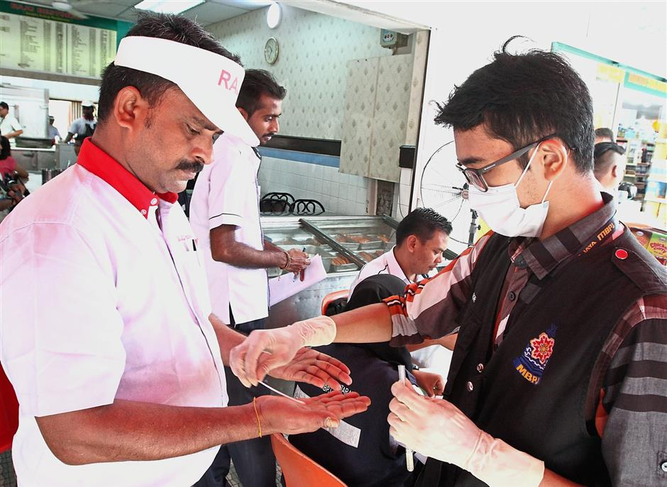 An MBPJ health officer taking swabs from the hands of a restaurant worker.