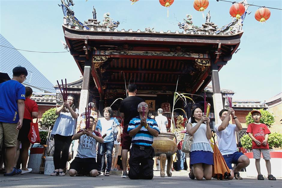 Devotees praying with joss sticks at the Snake Temple to commemorate the resident deity's birthday.
