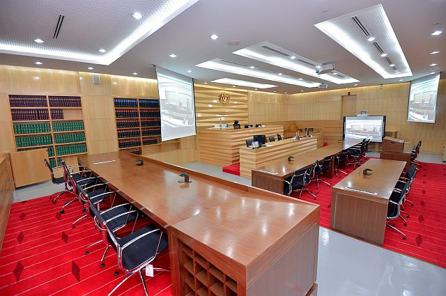 New layout of the high-tech equipped Construction Court in the Jalan Duta High Court. The judge now sits along the breadth of the room. The two screens hanging from the ceiling project the same image on the interactive white board so everyone in the court can view the same thing at the same time. The two rows of tables for counsel facing the judge are also equipped with moveable lecterns, microphones and points to plug in laptops so they can view the same image on the white board on their personal computers. The front row of the public gallery has been converted into an area where more than one expert witness can testify using the microphones on the tables.