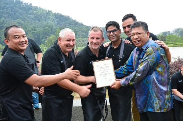 Zulkernai (right) presenting a token of appreciation to Le Meridien Kuala Lumpur executive chef Antoine Rodriguez (second from left) and Marriott International Asia Pacific representatives. (Right) The chefs serving food to the children.