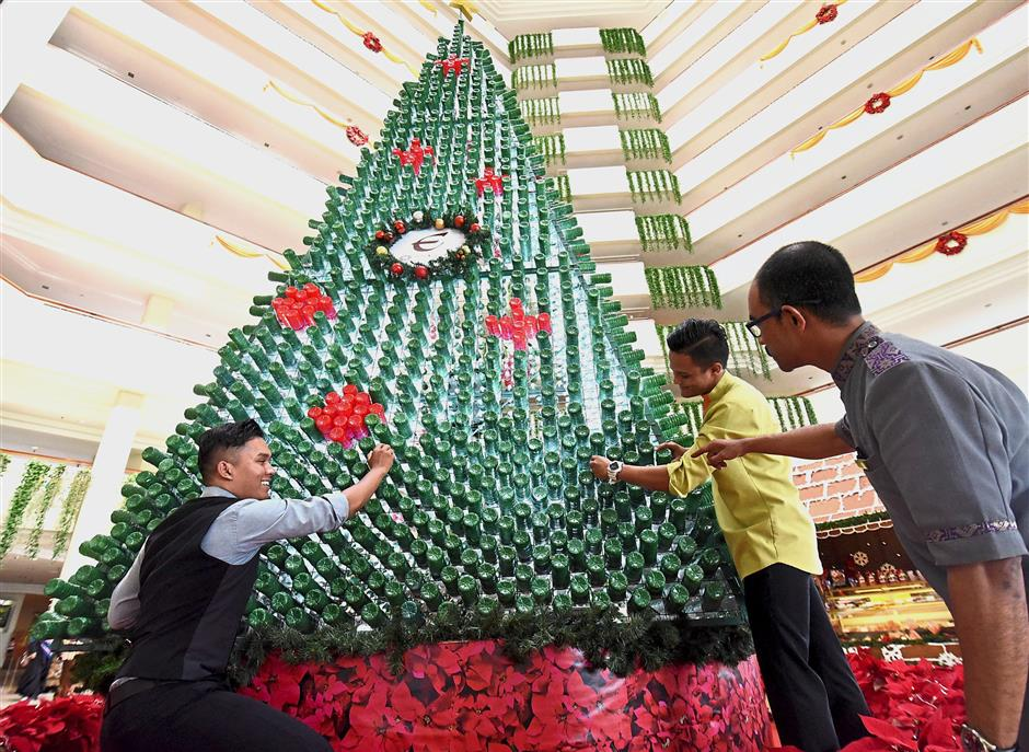 Hotel Equatorial Penang staff (from right) Abdul Karim Majid, Muhammad Aliff Shukeri and Shamsul Buqari Shaari arranging some of the 3,000 recycled plastic bottles on the 7m Christmas tree.