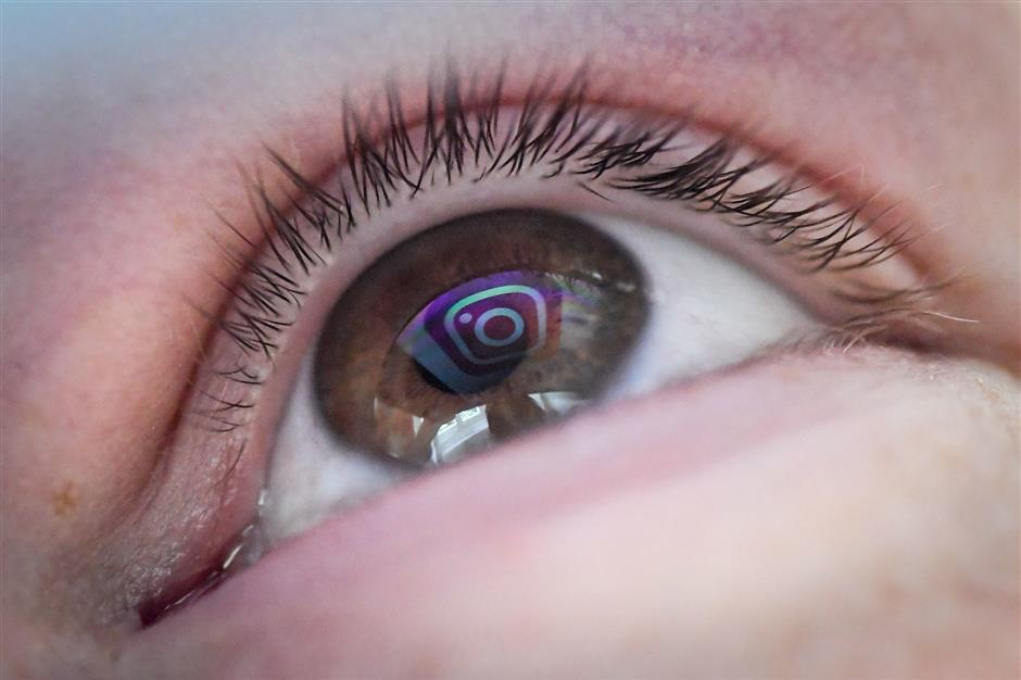 The logo of US social network Instagram is reflected on a woman\'s eye, on May 2, 2019 in Nantes, western France. (Photo by LOIC VENANCE / AFP)