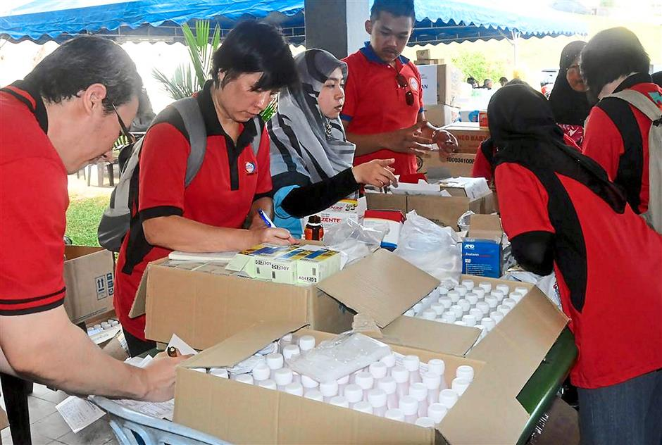 Keeping check: Volunteers dispensing medicine to flood victims during their visit.