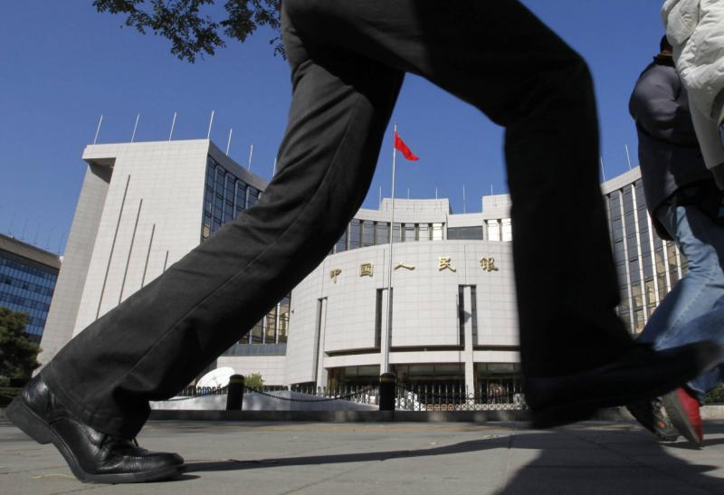 A pedestrian walking past the headquarters of the People\'s Bank of China in Beijing. The central bank held back from liquidity operations for the second day running on Tuesday as regulators show signs of concern that loose liquidity might be fuelling another round of risky credit expansion - Reuters.