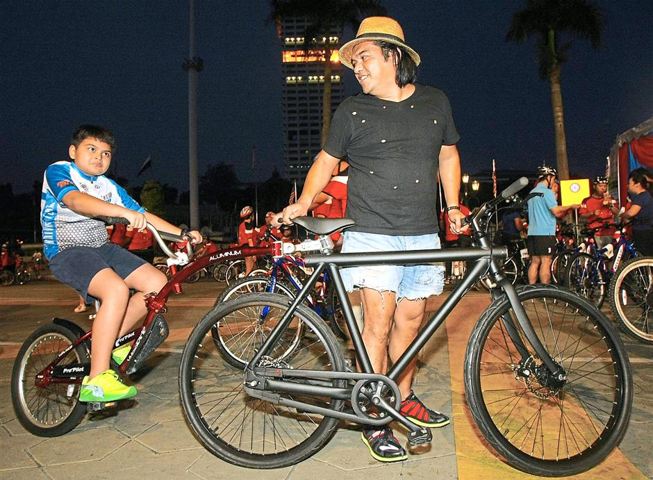 Rezzuan Tajuddin (right), and his son Izzrezza Rezzuan, 9, with their unique bicycle during KLSCCCIs Carbon Neutral Activities 2 - KL City Eco Charity Bicycle Ride.