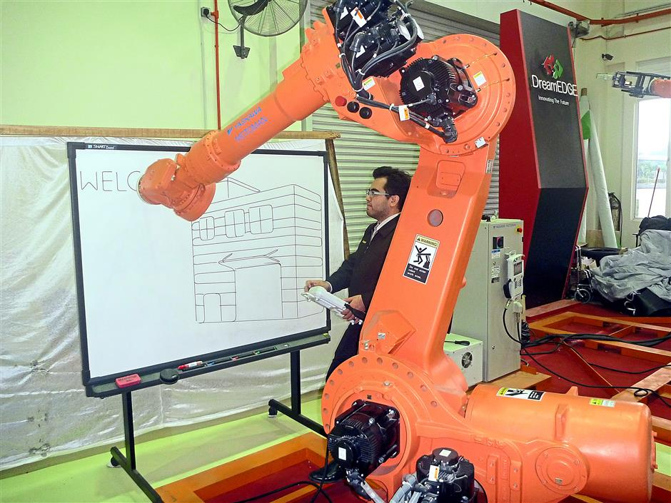 An engineer demonstrating how a manufacturing robot can be programmed for even the most delicate tasks, including drawing.
