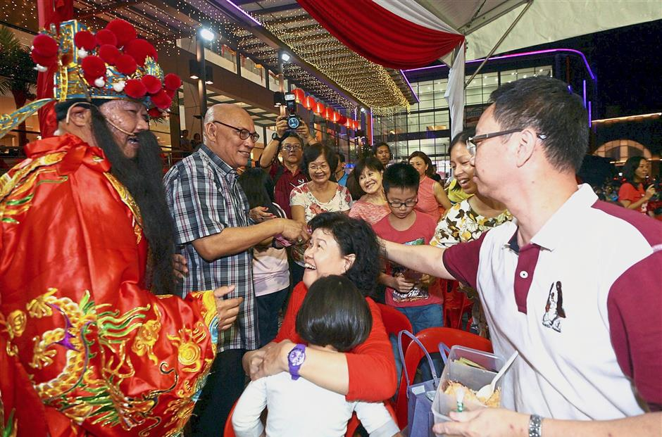Nor Hisham (second from left), seen here distributing ang pow to people who attended an MPSJ Chinese New Year celebration last year, is tipped to be the next Kuala Lumpur mayor. — Filepic