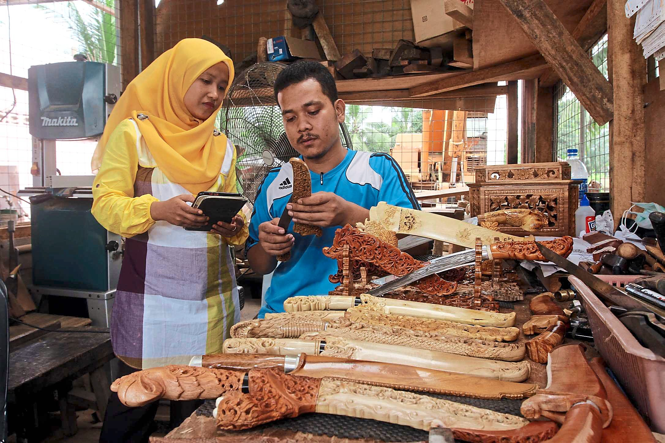 Handy income: Nooratikah and her husband Kamarulzaman made their handicraft in Kampung Sungai Satan,Jeli and sold it via word of mouth for three years. The couple now make five times as much, since creating a Business Facebook page .