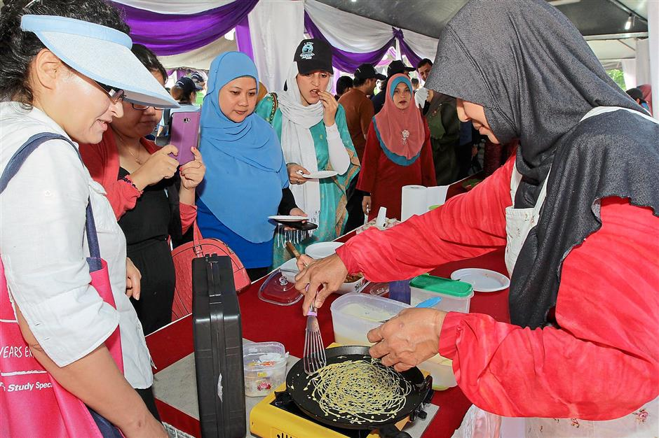 Web-like pancake: Visitors watching closely as a stall operator shows how to prepare roti jala during the event.