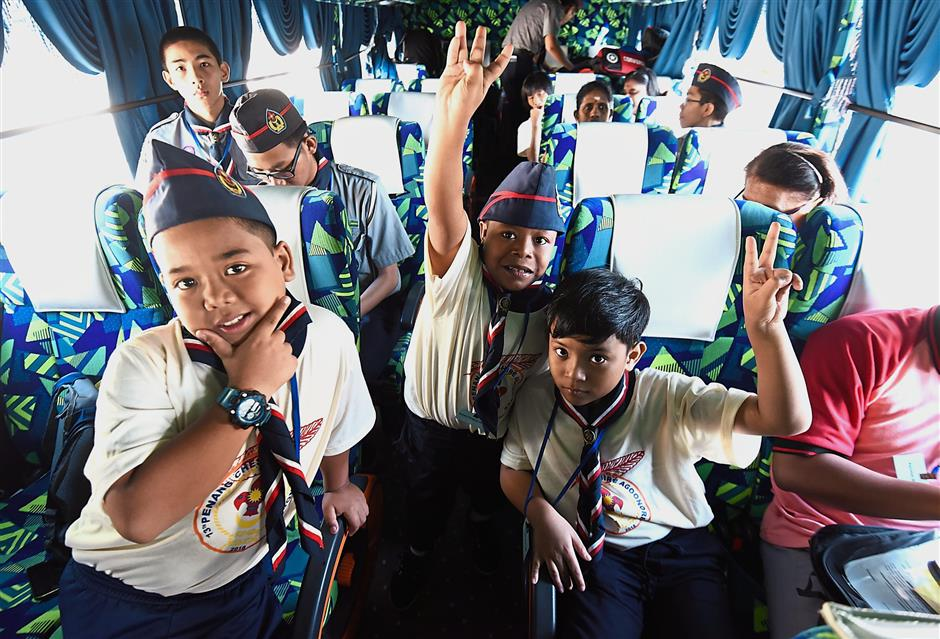 Three SK Pendidikan Khas Jalan Hutton special Scouts (from left, in front) Mohd Fakhrullah Rashidi, 11, Mohd Irman Firdaus Ismail, 10, and Mohd Izzul Adli Nordin, 10, in high spirits as they leave for the agoonoree.