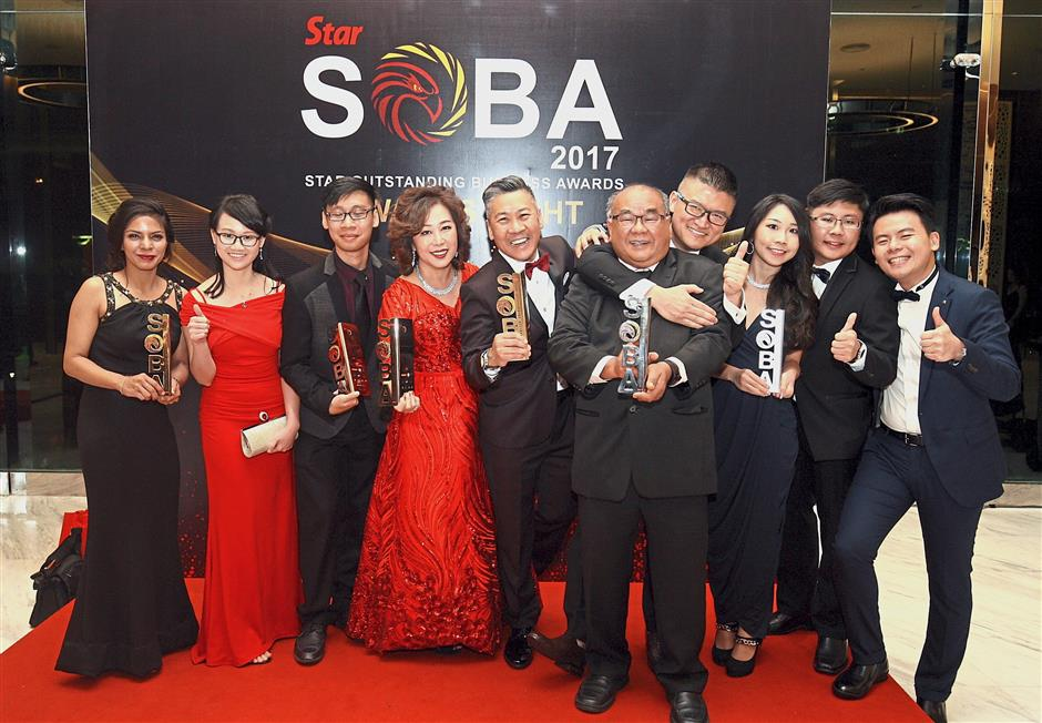 Choh (fourth from left), Lee (fifth from left) with their children and team celebrating their achievements for the Above RM25mil category: Gold for Best Brand, Silver for Best in CSR, Platinum for Best Employer, and Malaysian Business of the Year. Choh also won Female Entrepreneur of the Year award while Proguard Safety Manufacturing Sdn Bhd won Platinum for Best Global Market (Up to RM25mil category).