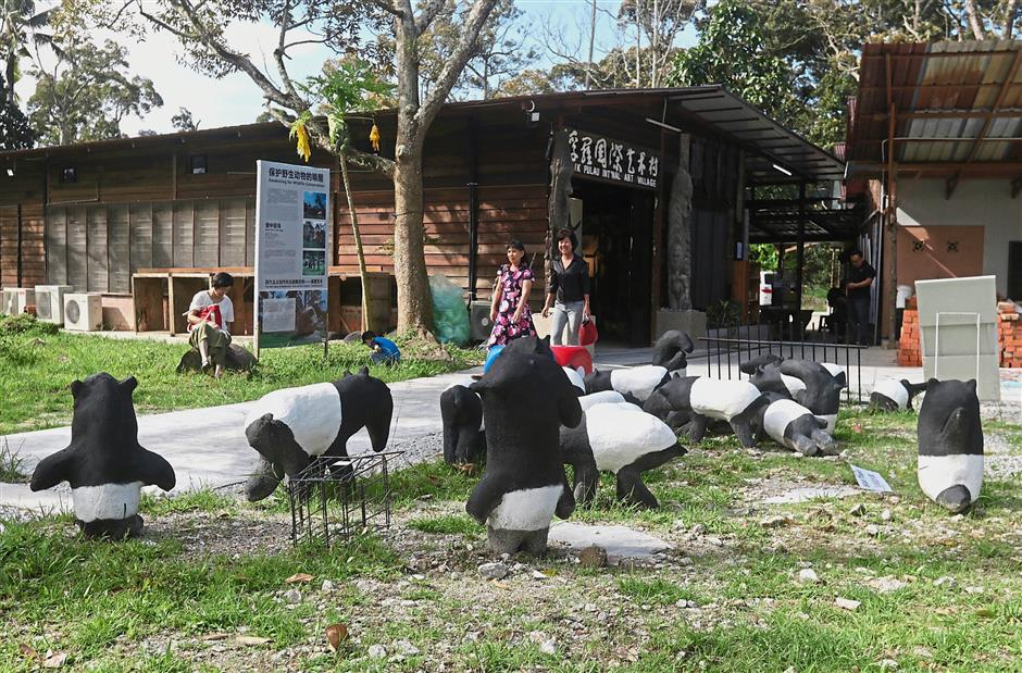 Visitors checking out the facilities and artworks at the Balik Pulau International Art Village in Penang. The compound of the art village is adorned with cute sculptures of tapirs in conjunction with the Art On Wildlife Conservation International Art Exchange.