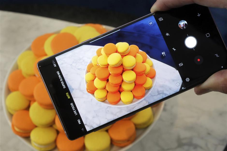 The Samsung Galaxy Note 9 is shown in this photo, in New York, Tuesday, Aug. 7, 2018. The camera in the Note 9 will use artificial intelligence to detect what's in a scene, whether that's food, flowers or a sunset, and to automatically tweak images to make them pop. (AP Photo/Richard Drew)