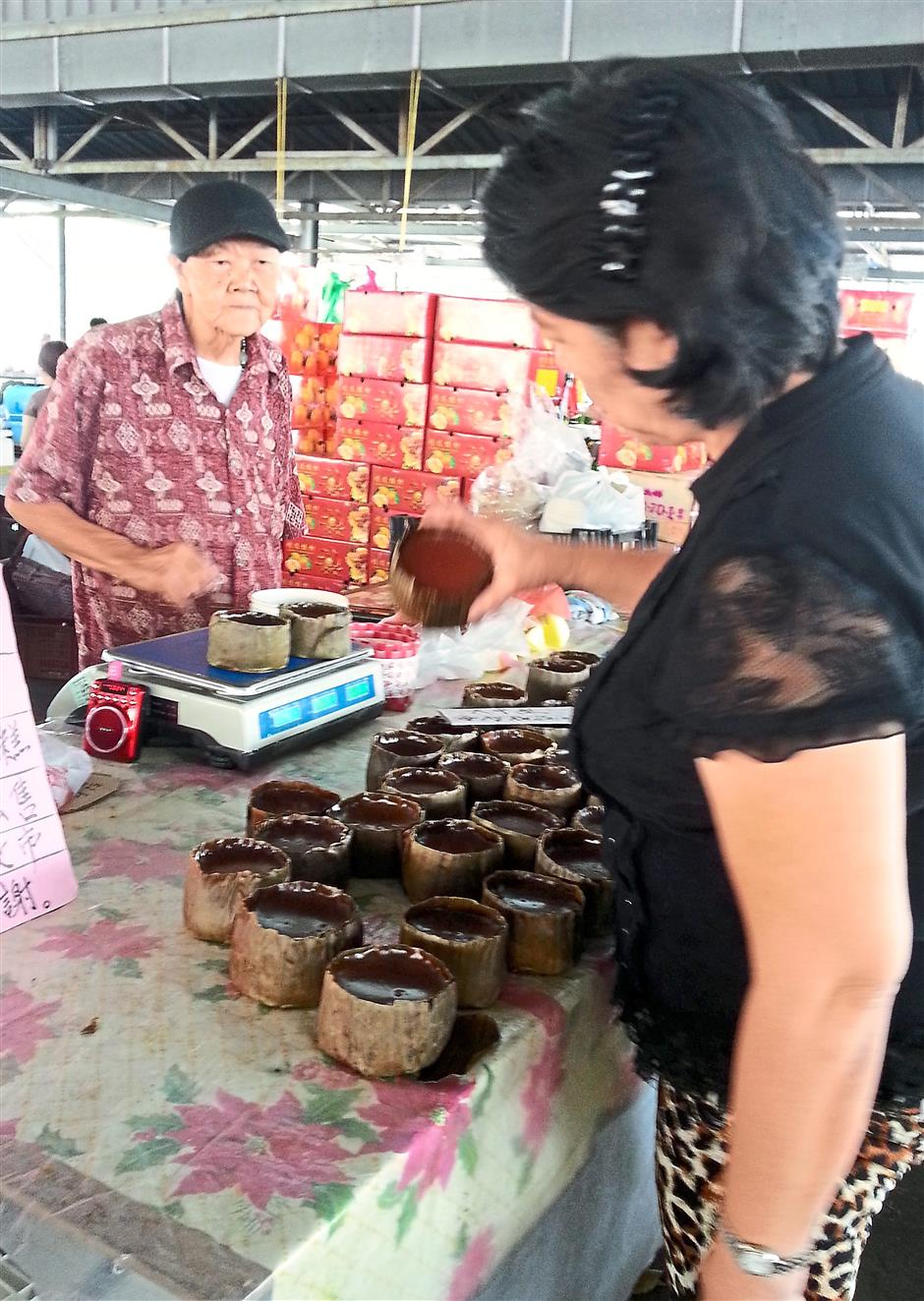 Careful selection: Oh (left) with a customer at his stall in SPPK wet market in Pengkalan, Ipoh.